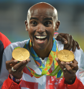 Mo Farah shows off his medals at the podium during the Rio 2016 Olympic Games. Photo By Tim Hipps, U.S. Army IMCOM Public Affairs . U.S. Army - via Wikimedia Commons.