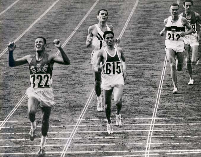 "Billy Mills winning the 10,000m in the 1964 Olympics: 1stLt William ""Billy"" Mills, USMCR (No. 722),[1] wove through a field of lapped runners and passed the race favorite, Ron Clarke (No. 12, ""1"" visible on shirt)[1] of Australia, to win the 10,000 meters race at the 1964 Olympic Games. His victory is described as one of the greatest upsets in Olympic history and he is still the only American to ever win a gold medal in that event. Mohammed Gammoudi (615)[1] won the silver medal. Photo: Public domain as a work of the U.S. Marine Corps"