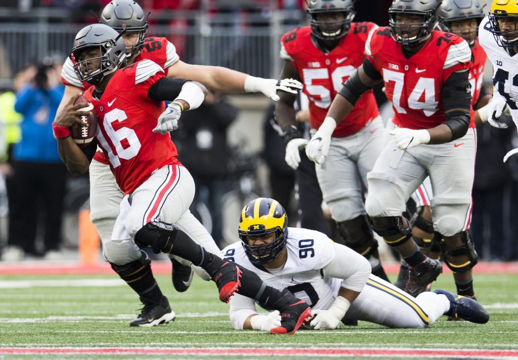 Nov 26, 2016; Columbus, OH, USA; Ohio State Buckeyes quarterback J.T. Barrett (16) escapes a tackle attempted by Michigan Wolverines defensive tackle Bryan Mone (90) in the third quarter at Ohio Stadium. Ohio State won the game 30-27 in double overtime. PHOTO: Greg Bartram-USA TODAY Sports